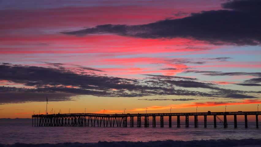 VENTURA, CALIFORNIA - CIRCA 2015 - A gorgeous red orange sunset coastline shot along the Central California coast with the Ventura pier distant. | Shutterstock HD Video #12932786
