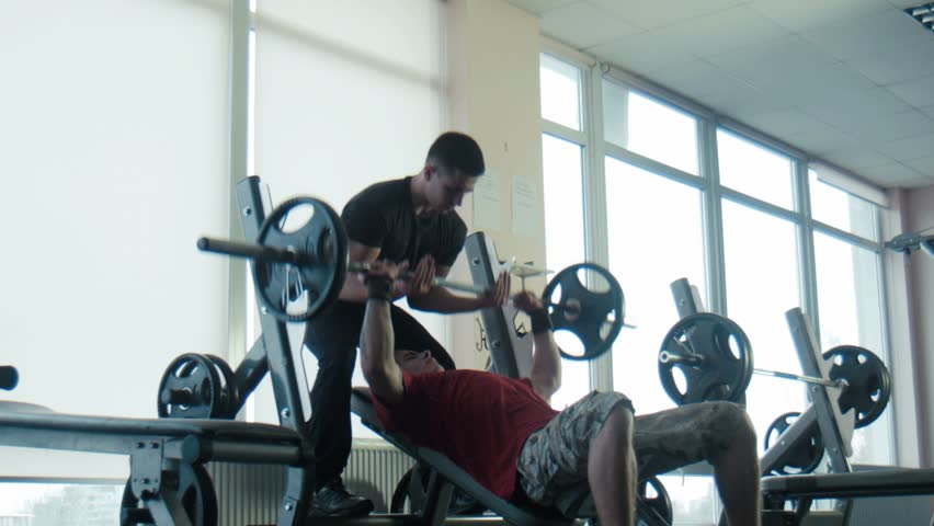 The bodybuilder does exercise with a bar, the trainer holds a bar