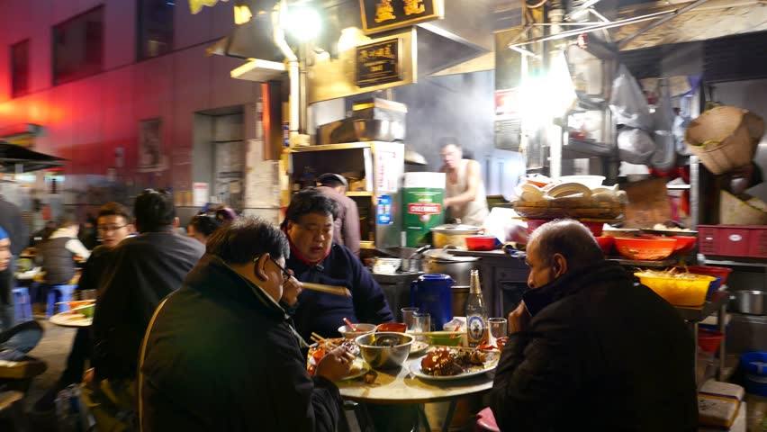 HONG KONG - FEBRUARY 10, 2015: Authentic outdoor eatery on dark urban alley, people seat and eat supper, POV walk through pedestrian street, crowded by noshery kiosks, night outside kitchen being work