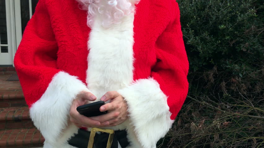 Santa Claus texting and shopping on his cell phone - 4K stock video clip