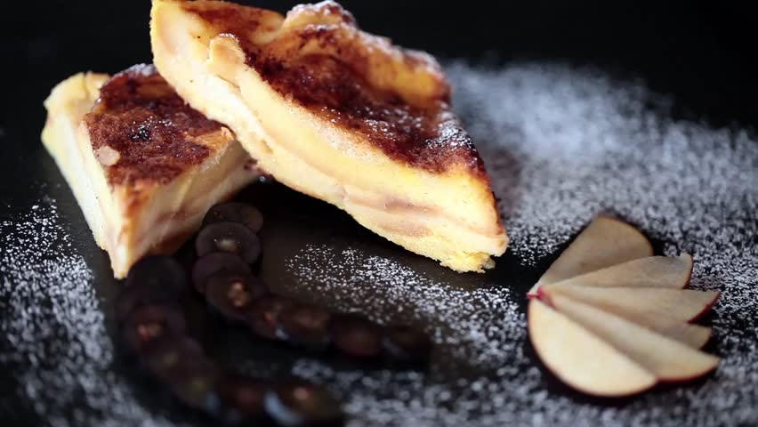 Video clip of slices of bread and butter pudding with icing sugar sifted above.