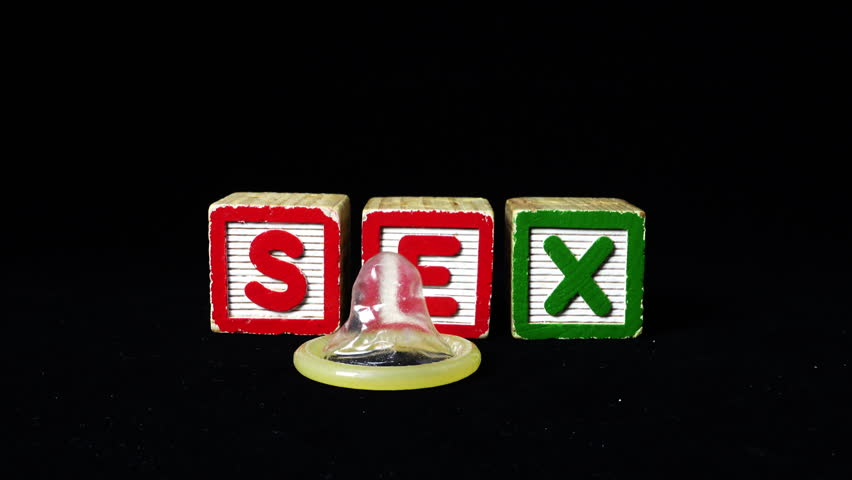 Condom falls/throwns near Alphabet Blocks spelt SEX. Black Background. 4k Video. Safe sex & healthy lifestyle concept. - 4K stock footage clip