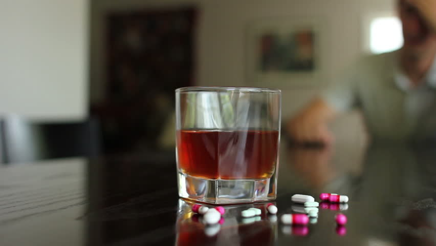 Substance abuse, pan shot of pills and alcohol out of focus man in background