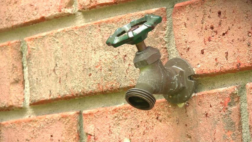 Outdoor Garden Hose Spigot Protruding From A Brick Wall Leaks Dripping Water Stock Footage