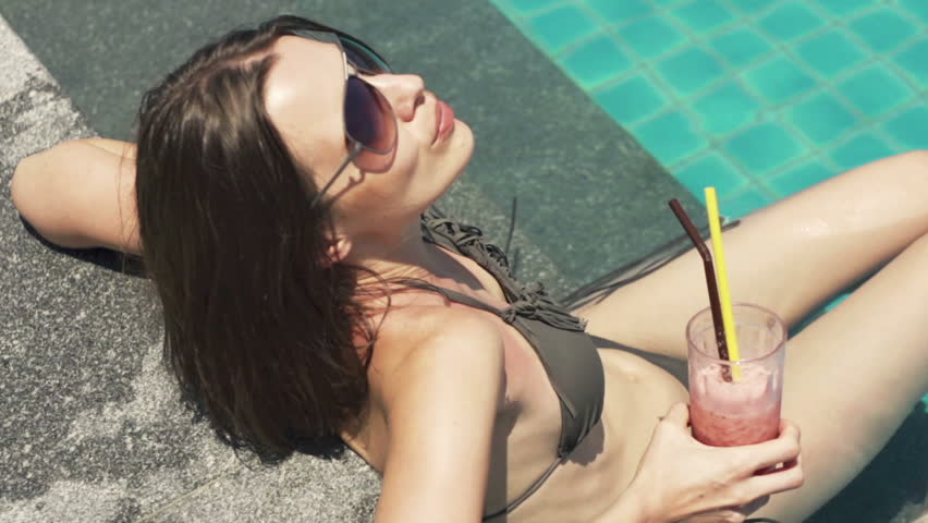 Pretty woman drinking cocktail by swimming pool