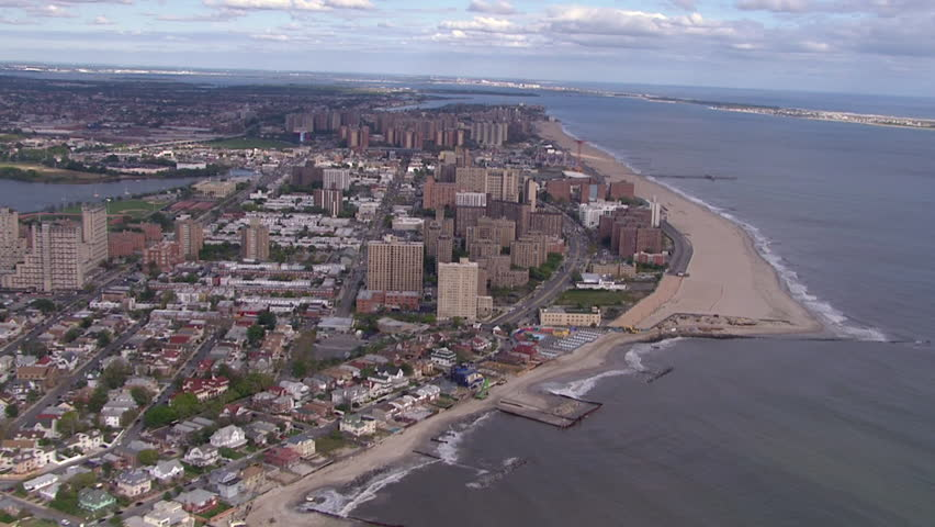 Aerial view of Coney Island amusement Park, Luna Park, in Brooklyn New York on a beautiful cloudy day. Tourists and families come for fun and rides.(Coney Island, NY - 2014). - HD stock footage clip