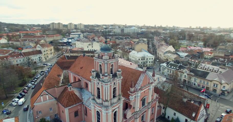 AERIAL. Smooth 360 orbit flight around beautiful Church of All Saints (Visu Sventuju) in Vilnius old town, Lithuania. Panorama of Vilnius