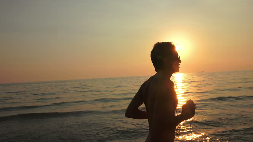 Young man with headphones run at sea at sunrise. He makes a run along the sea coast. camera stabilized shots. Closeup | Shutterstock HD Video #13145744