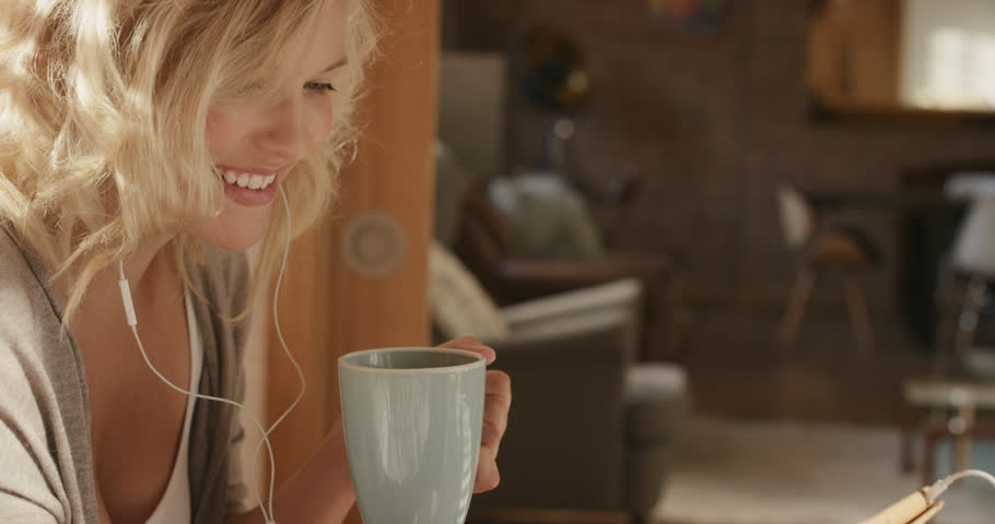 Beautiful blonde woman at home using digital tablet technology to connect drinking coffee in bed