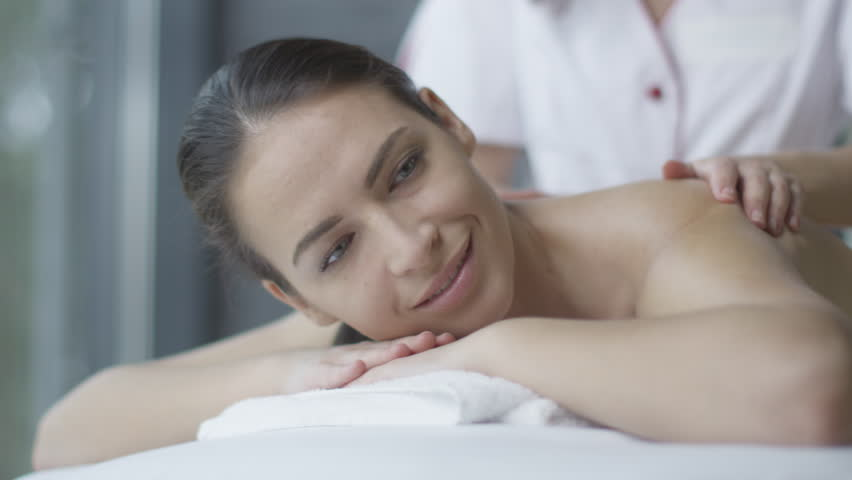 Beautiful woman is getting a relaxing massage from a female masseur in wellness center. Shot on RED Cinema Camera in 4K (UHD). - 4K stock video clip