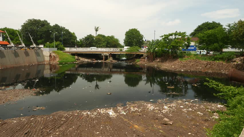 JAKARTA, INDONESIA - MARCH 09, 2015: Kali Ciliwung estuary pond in front of Sunda Kelapa harbor, ecological issue - black water with chemical polluted and trashed with floating garbage - 4K stock video clip