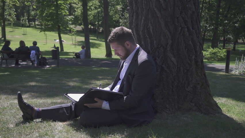 Businessman makes notes sitting under tree in the park, pan shot. - HD stock footage clip