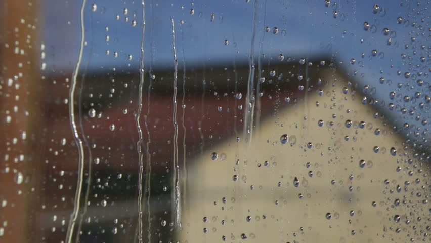 heavy rain falling against large window pane  raindrops trickle down  grey sky with london