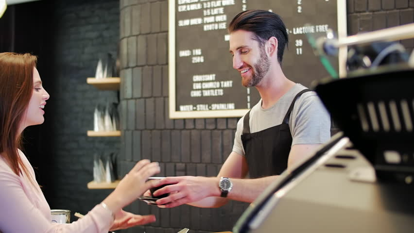 Hipster barista serves coffee and interacts with customers in modern trendy coffee shop cafe