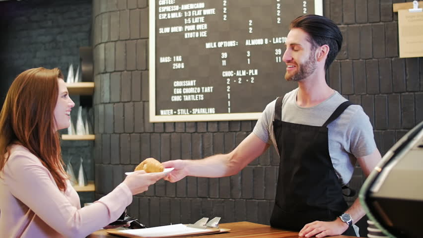 Hipster barista with beard hands takeaway coffee to customer who makes mobile online cashless electronic payment with mobile cell phone in modern trendy coffee shop cafe