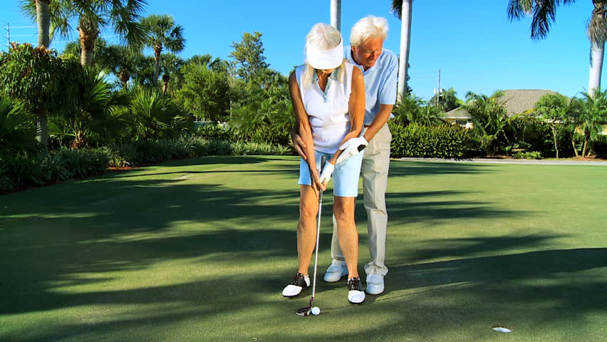 Senior gentleman teaching his wife to play golf in retirement  filmed at 60FPS - HD stock video clip