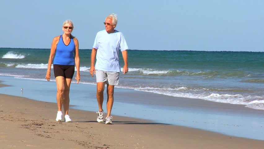 Healthy senior couple keeping fit in their retirement walking on the beach filmed at 60FPS - HD stock video clip