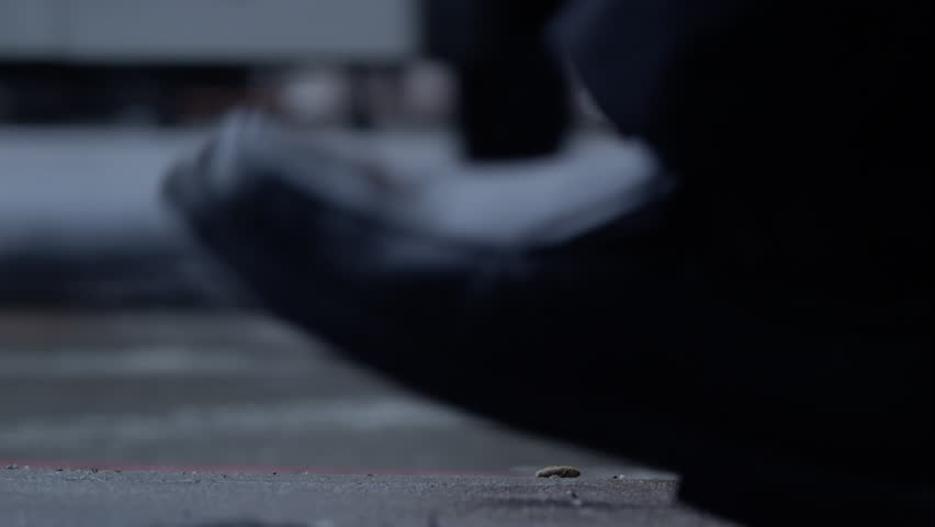 Feet in dress shoes walking by on the street until high heels walk by in focus at the end- camera low on ground as cars pass by - HD stock footage clip