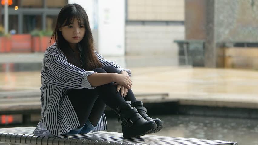 Young Sad Girl Sitting Alone While Rain Falls Behind ...