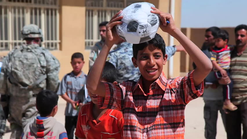 CIRCA 2010s - U.S. soldiers hand out water filters, toys and school supplies to people in Baghdad, Iraq.