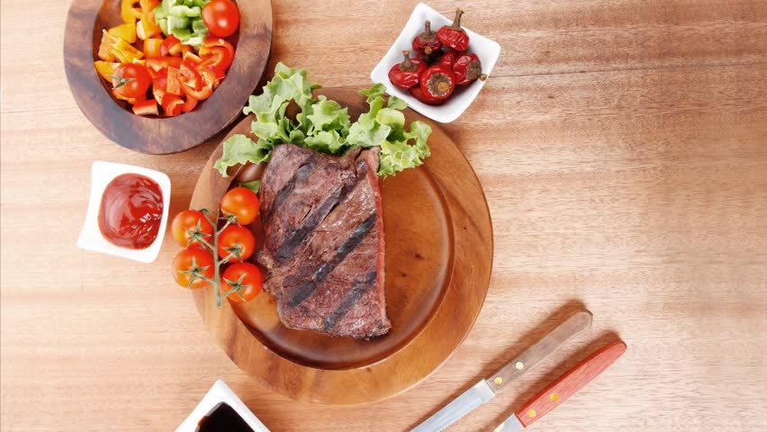 fresh rich juicy grilled beef meat steak fillet with marks on wooden plate over table decorated with lettuce salad and cutlery new york styled cuisine 1920x1080 intro motion slow hidef hd