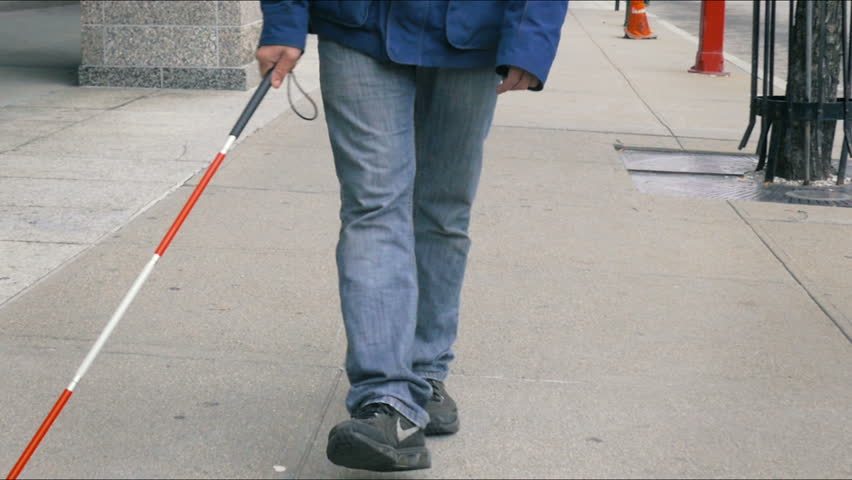 Blind person feet walking with cane closeup