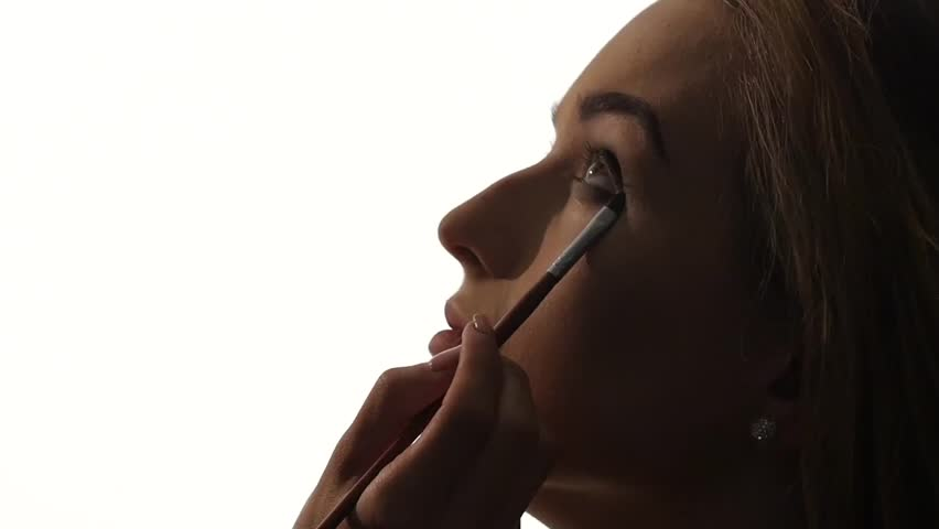 Eye makeup woman applying eyeshadow powder, Close up, Make-up artist applying bright base color eyeshadow on model's eye and holding a shell with eyeshadow, silhouette. Slow motion - HD stock footage clip