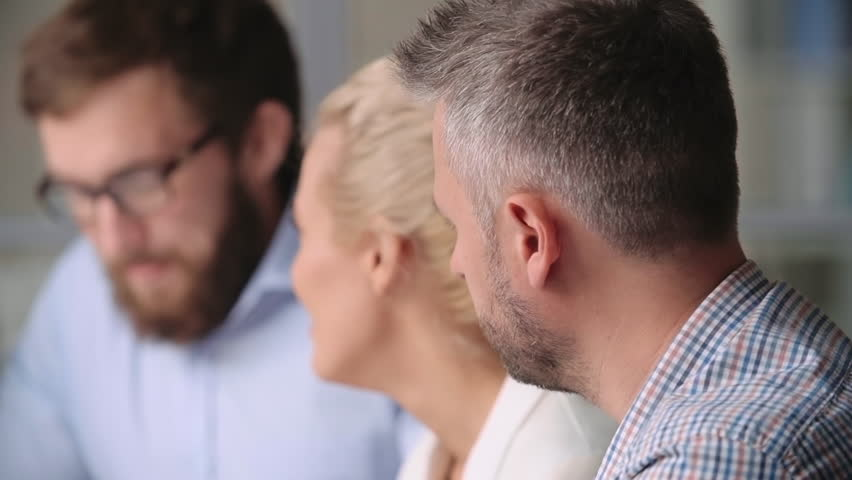 Close-up of man getting bored at the meeting and stopping paying attention what his colleagues talking about - HD stock video clip