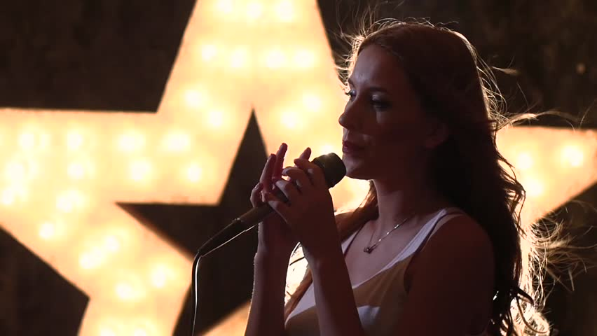 Beauty Glamour Singer Girl. Rock n roll Style. Song. Stylish girl singing with a microphone, closed eyes singing, female singer with microphone, music hall, the scene, shining star in the background