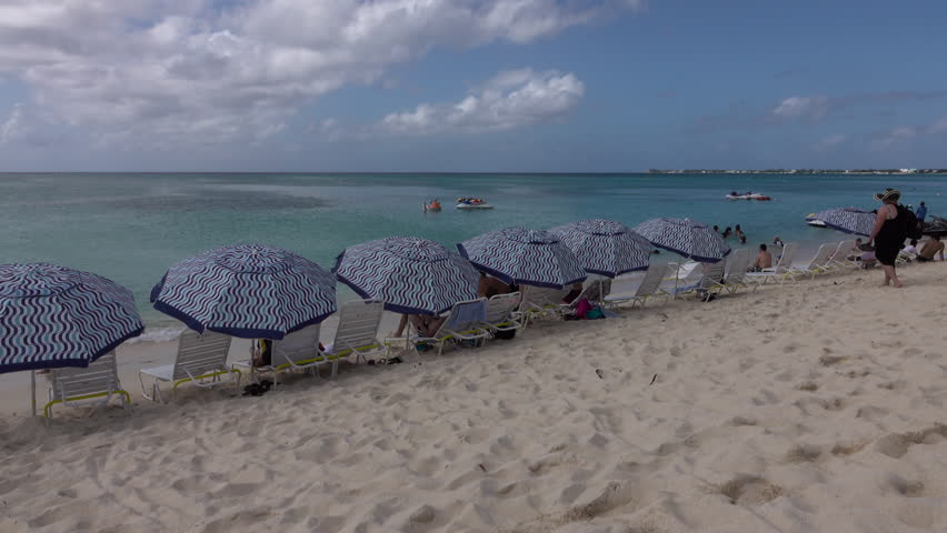GRAND CAYMAN - NOV 2015: Grand Cayman Island Caribbean sandy beach umbrellas 4K. Cruise ship and vacation travel. Sunshine and white beach. Beach, scuba diving and resorts cater to tourists.
