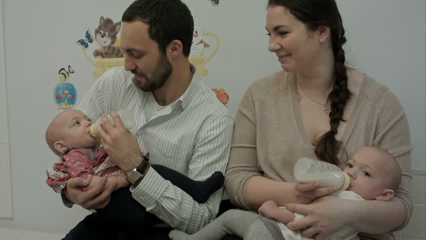 Young couple feed newborn twins from a bottle