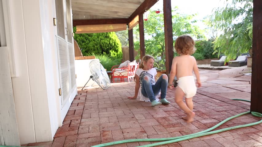 9 year old girl and 2 year old toddler boy playing on patio - HD stock footage clip