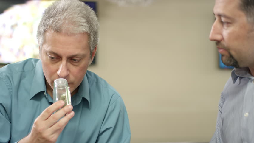 Older customer at a recreational marijuana shop looking closely at product, smelling it and smiling, close up