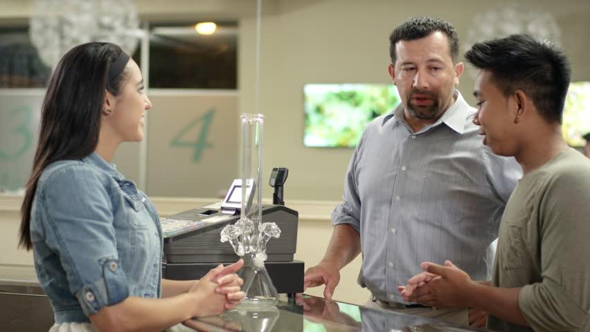 Customers checking out a large bong at a recreational marijuana shop