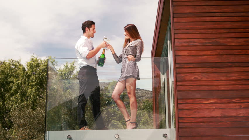 Smiling couple toasting with champagne on the balcony - HD stock video clip
