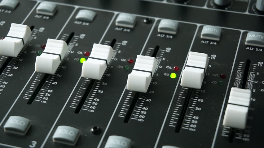 A mixing desk or mixing console being used to mix a track in a recording studio. With level and overload lights, faders and pots / knobs. Fingers adjusting the level of the faders.
