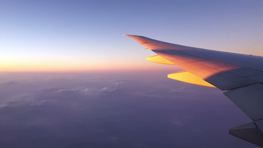 4K Traveling by Airplane at Sunset. View From Airplane Window. 4K Ultra HD 3840x2160 Video Clip