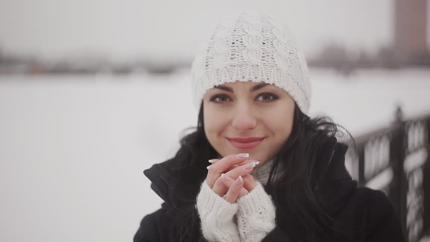 beautiful girl warms the palms near the river in winter - HD stock video clip