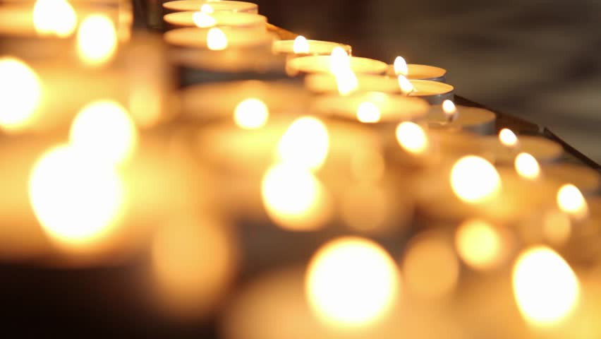 Lighted candles on table in Catholic Church. Lots of candles with shallow depth. Small candles.
