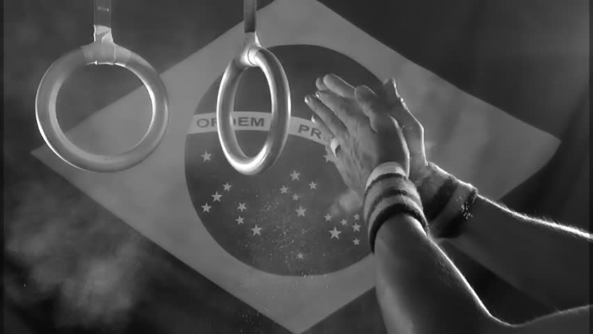 Taped hands of gymnast clapping white chalk powder into a cloud under gymnastic rings in front of a Brazil flag background in gritty black and white