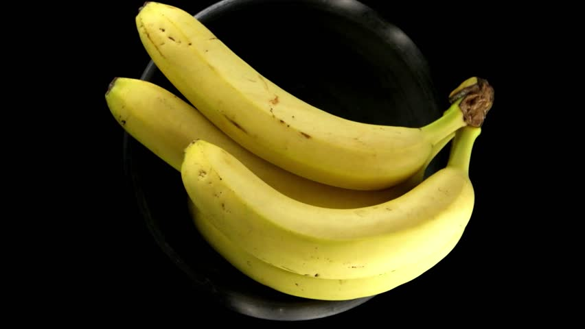 Bananas rotating on a black background. - 4K stock footage clip