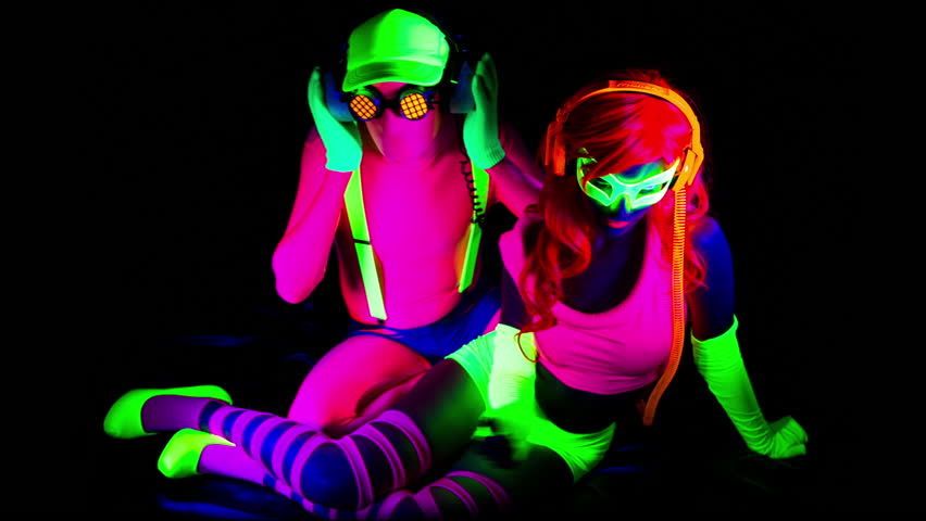 fantastic video of sexy cyber raver man and woman filmed in fluorescent clothing under UV black light - HD stock footage clip
