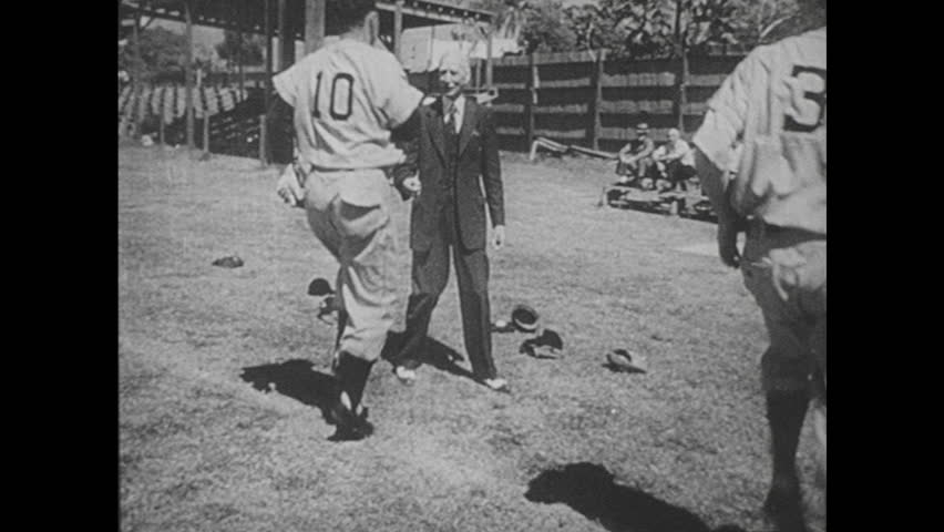 UNITED STATES 1940s: Baseball players exercising, Connie Mack talks to players / Wipe to women working at desk / View of woman / Women at desk / Wipe to Winston Churchill walking through crowd.