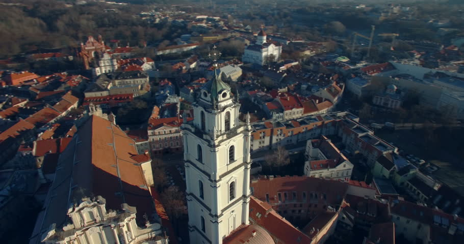 AERIAL. Smooth orbit flight around Sts Johns' Church (Sv. Jonu baznycia) in Vilnius. Beautiful view of old town of capital of Lithuania. 4K