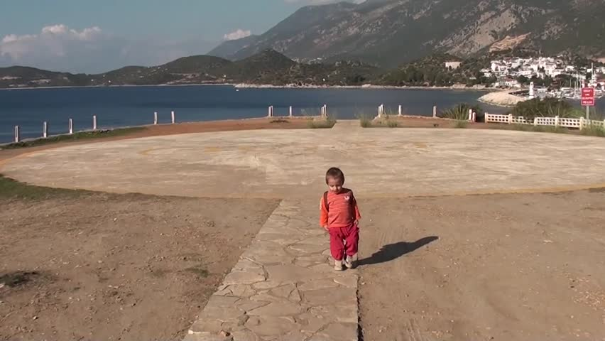 Cute toddler walking alone on helicopter platform