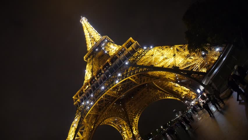 Paris, France - October, 2015 - Low angle show of the sparkling lights on the Eiffel Tower at night.