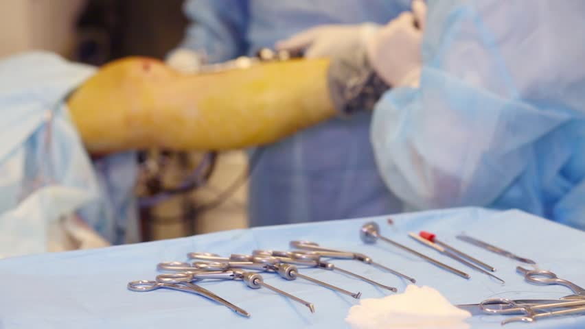 Doctor carries out endoscopic surgery in leg joint. Focus on tools