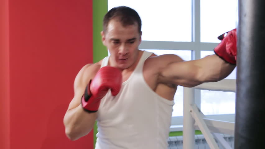 Boxing classes. A man is engaged in Boxing with a Punching bag