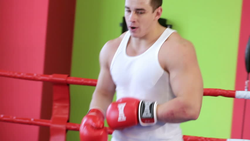 Training boxer. Kickboxer is working out blows in the ring closeup