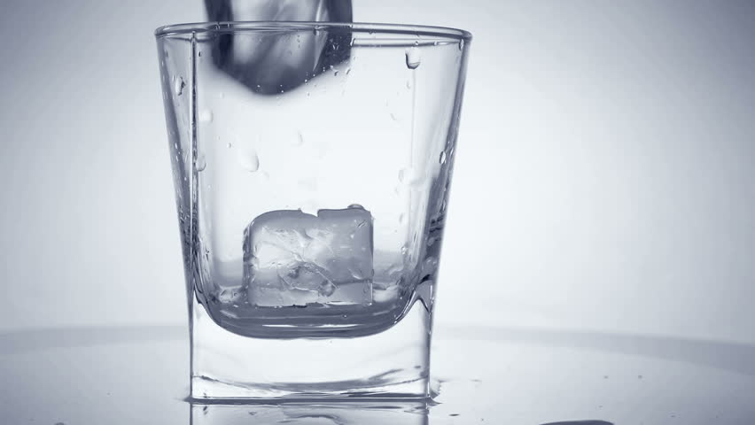 Glass with ice cubes. White background. Close-up. - HD stock footage clip